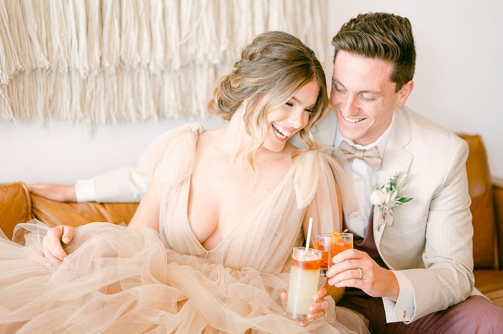 Bride and groom drinking a cocktail and clanking glasses by Amy Huang Photography a San Diego Wedding Photographer