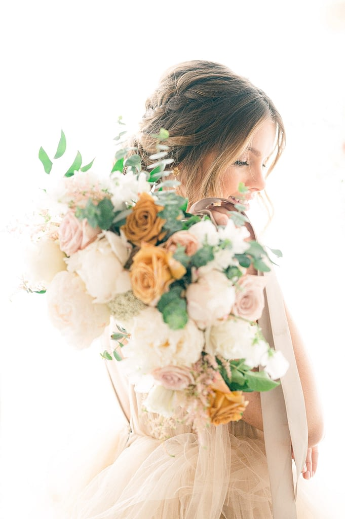 Photo edited by Refined Preset KT Merry of a Beautiful Bride holding a neutral colored bouquet with gold roses.