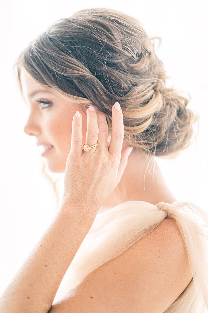 Photo edited by Refined Preset KT Merry of a bride wiping her hair away, focus on the ring and with her face delicately blurred.