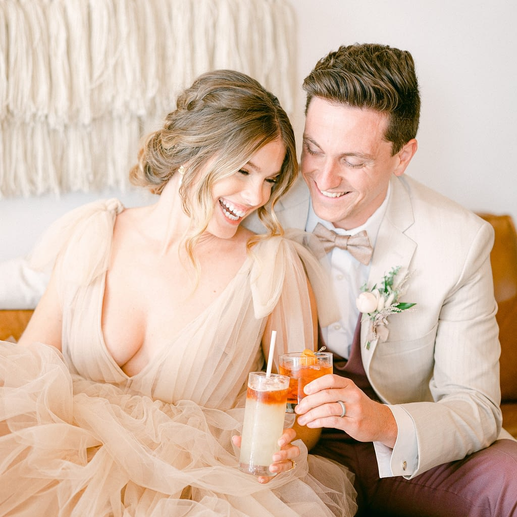 Bride and Groom holding cocktails and laughing and having a great time | a photo by Amy Huang Photography a Wedding Photographer in San Diego