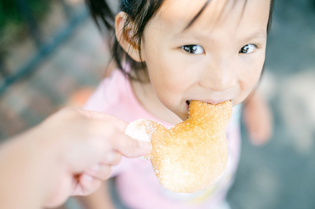 Little girl eating mickey mouse beignet at Disneyland   Photo taken by Amy Huang Photography   A San Diego Photographer