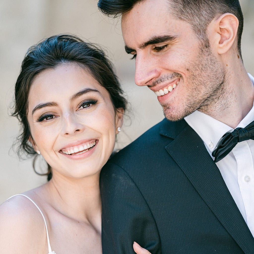 Beautiful and happy bride smiling at camera while groom smiles at his bride by Amy Huang Photography a San Diego Photographer
