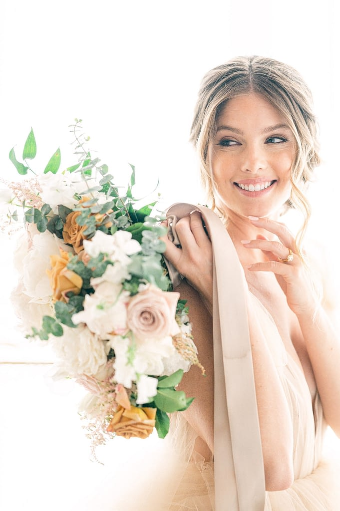 Photo edited by Refined Preset KT Merry of a beautiful bride holding a bouquet and laughing towards the side of the camera.